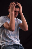 Upset teenager with head in hands wincing from stress, anguish o Stock Photography