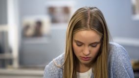 Upset teenager looking at two strips on pregnancy test, feeling desperate, fear stock images