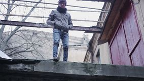 Upset teenager about to commit suicide by jumping from roof, changing his mind. Stock footage stock footage