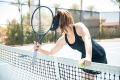 Upset tennis player after losing the point. Upset female tennis player standing by the net after losing the point during tennis match on outdoor court Stock Photos