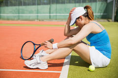 Upset tennis player sitting on court. On a sunny day Stock Photo