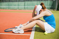 Upset tennis player sitting on court. On a sunny day Stock Images