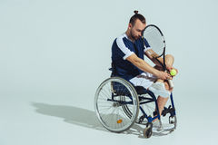 Upset tennis player sitting in wheelchair and holding tennis racquet and ball Royalty Free Stock Photo