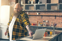 Upset thick guy staring at computer with dissatisfaction royalty free stock photo