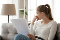 Upset thoughtful woman holding paper document in hands, sitting on sofa. Looking in distance, thinking about received bad news, notification, checking bills stock photography