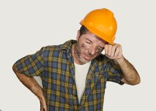 Upset and tired construction worker or repair man wearing builder helmet complaining suffering pain in his lower back feeling royalty free stock photography