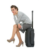 Upset traveling woman sitting on suitcase Stock Image