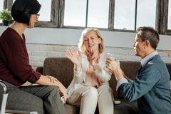 Upset and unhappy good-looking woman actively gesturing and explaining. Caring men supporting. Upset and unhappy good-looking women actively gesturing and stock photo