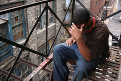 Upset Urban Teen Male. Upset African American teen male on rusty fire escape of building, head in hands. Urban setting with old buildings in background Stock Image