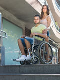 Upset wife with man in wheelchair on stairs Royalty Free Stock Image