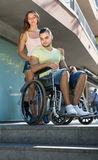 Upset wife with man in wheelchair on stairs Royalty Free Stock Images