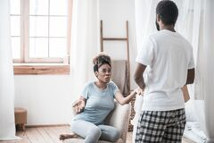 Upset wife sitting and husband standing with back