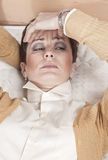 Upset woman. Lying down and holding hand on her forehead. Looking away Royalty Free Stock Photos