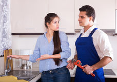 Upset woman annoying handymen with complains Stock Photos