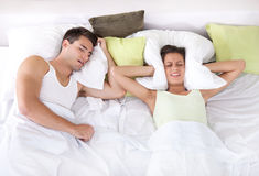 Upset woman in bed with her boyfriend snoring. Couple in bed; men snoring and women can not sleep; covering ears with pillow for snore noise Stock Images