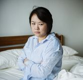 An upset woman in a bed room Stock Photos