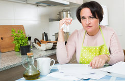 Upset woman with bills crying at home Stock Photography