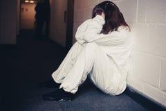 Upset woman in boiler suit sitting in corridor Stock Photos