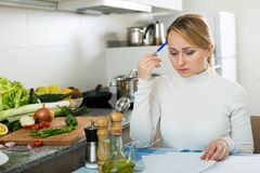 Upset woman calculating budget in kitchen Royalty Free Stock Images