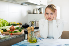Upset woman calculating budget in kitchen Stock Photo