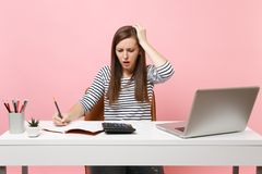 Upset woman clinging to head using calculator writing notes with calculations sit and work at office with pc laptop royalty free stock photography
