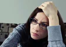 Upset woman. Close up of a young worried brunette wearing glasses Stock Image