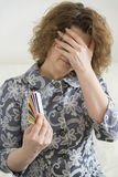 Upset woman with credit cards covered  face his hand Royalty Free Stock Photo