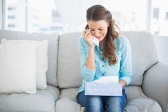 Upset woman crying sitting on sofa stock images