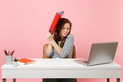 Upset woman defending hiding behind red folder with paper document work on project while sit at office with laptop royalty free stock photo