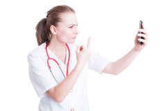 Upset woman doctor showing middle finger over video call Stock Images