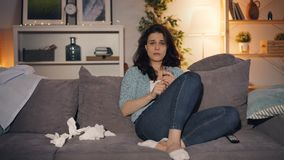 Upset woman drinking alcohol crying watching sad movie on TV at home alone
