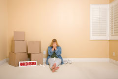 Upset Woman on Floor, Boxes and Foreclosure Sign Stock Image