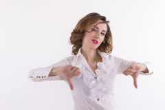 Upset woman giving thumbs down gesture on a white background. Studio shot Royalty Free Stock Photo