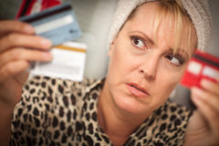 Upset Woman Glaring At Her Many Credit Cards Stock Photography