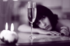 Upset woman with glass of drink and candel lights Royalty Free Stock Photography