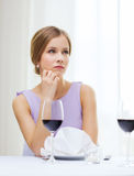 Upset woman with glass of whine waiting for date Stock Photography