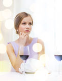 Upset woman with glass of whine waiting for date Stock Photos