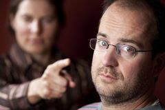 Upset woman and guilty man. Guilty man with upset woman in the background Royalty Free Stock Photography