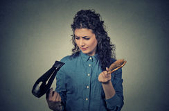 Upset woman with hair dryer and hair brush Stock Images