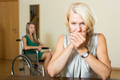 Upset woman and handicapped Stock Images