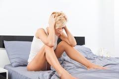 Upset woman head ache sitting on bed Stock Photo