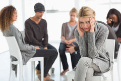 Upset woman with head in hands at rehab group looking at camera Royalty Free Stock Photos