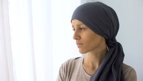 Upset woman in headscarf looking in window, rehabilitation centre, fatal disease. Stock photo royalty free stock image