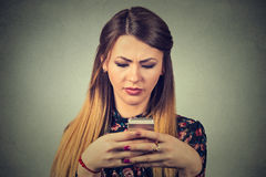 Upset woman holding cellphone. Sad looking girl texting on smartphone Stock Photos