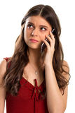 Upset woman holds cell phone. Red dress and small pendant. She heard unpleasant things. Don't be sad Stock Images