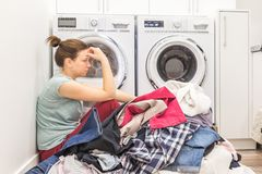 Upset woman in laudry room sitting ona floor with dirty clothes. Tired and frustrated stock photos