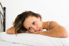 Upset woman laying in bed. With dropped eyes royalty free stock photos
