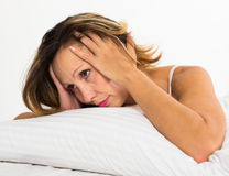 Upset woman laying in bed. Upset long-haired woman laying in bed with dropped eyes Stock Images