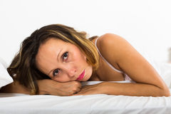Upset woman laying in bed Stock Image