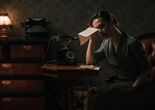 Upset woman with letter in retro interior. Beautiful young woman in retro interior stock photography